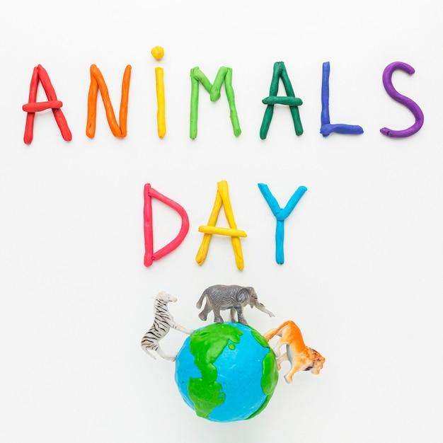 Vue de dessus de l'écriture colorée et de la planète terre avec des figurines d'animaux pour la journée des animaux