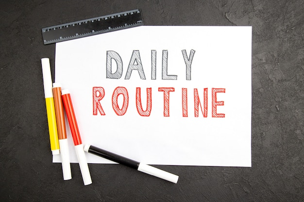 Vue de dessus écriture de routine quotidienne sur blanc avec des crayons sur une surface sombre note bloc-notes couleur cahier de couleur