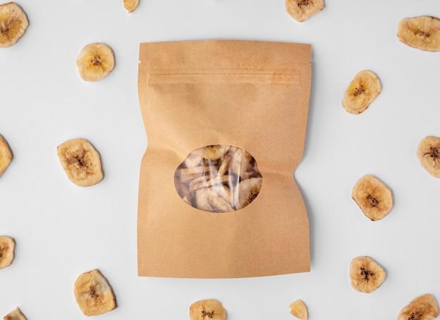 Vue de dessus de l'emballage en papier avec des tranches de banane séchée