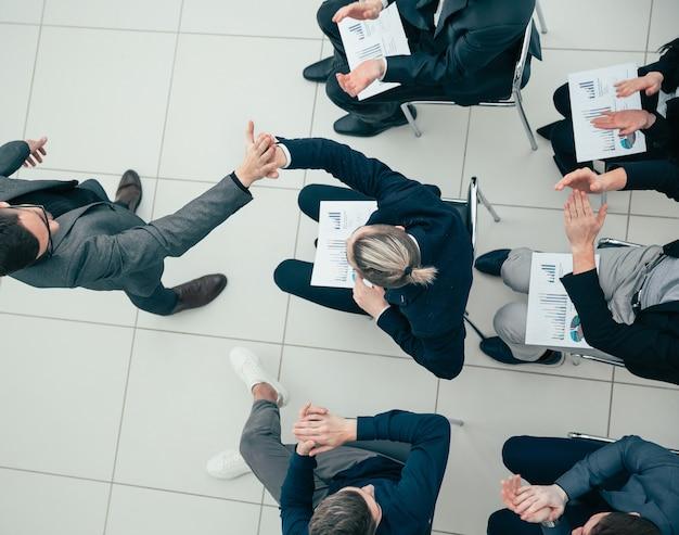 Vue de dessus. des employés heureux se donnant une note de cinq lors d'une réunion de travail.