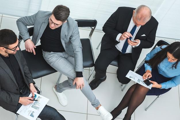 Vue de dessus des employés utilisant leur smartphone lors d'une réunion de travail