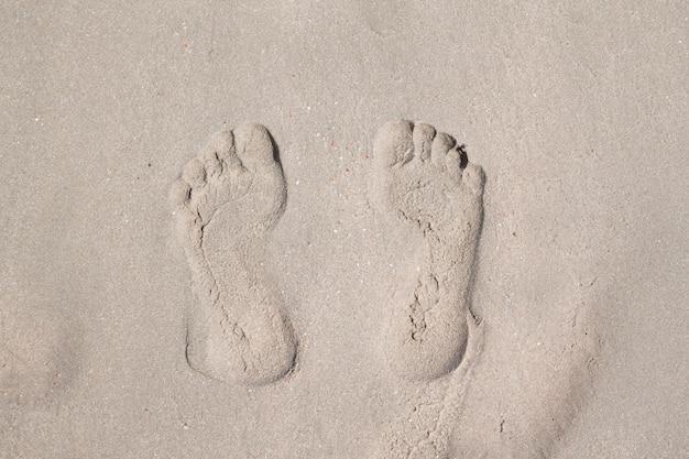 Vue de dessus des empreintes de pas sur la plage de sable