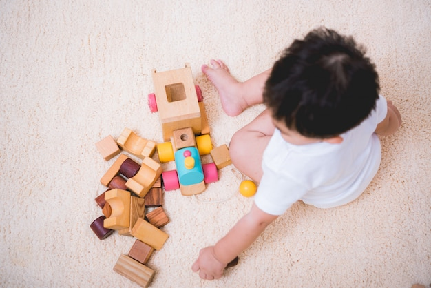Vue de dessus d'un enfant asiatique jouant avec des blocs de jouets