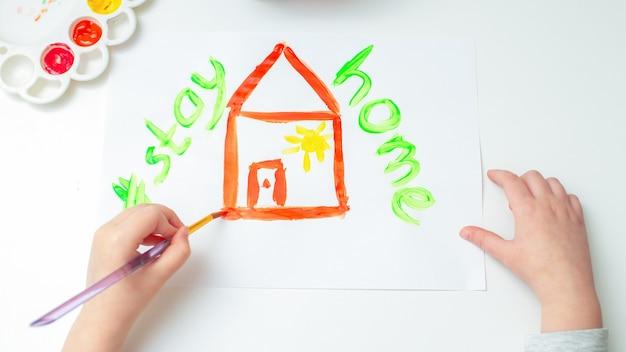 Vue de dessus, l'enfant dessine une maison rouge à l'aquarelle avec des mots restez à la maison sur une feuille de papier blanche. restez à la maison concept.