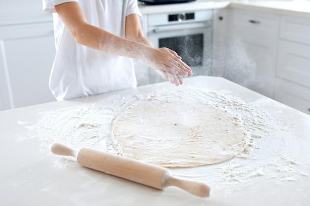 Vue de dessus d'un enfant faisant la pâte à pizza sur une table légère. verser la farine