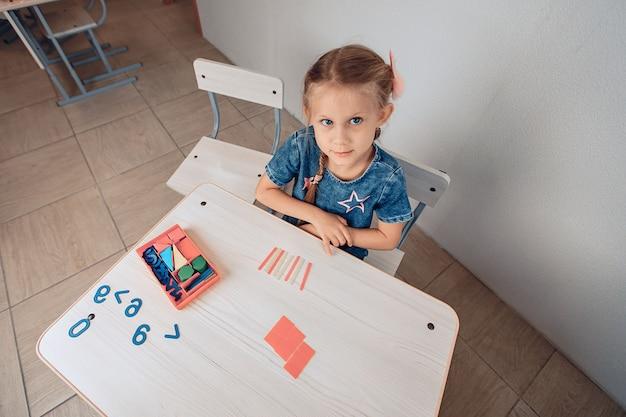 Vue de dessus d'un enfant féminin assez attrayant mignon assis à une table blanche où des puzzles logiques sont disposés. enfant regardant directement la caméra. concept de développement. photo avec du bruit
