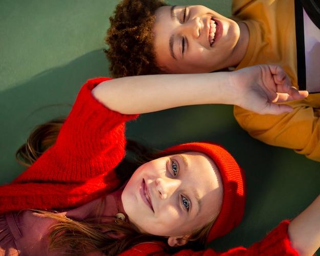Vue de dessus des enfants couchés ensemble sur un terrain de basket