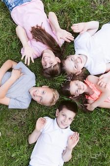 Vue de dessus des enfants heureux, souriant à la caméra