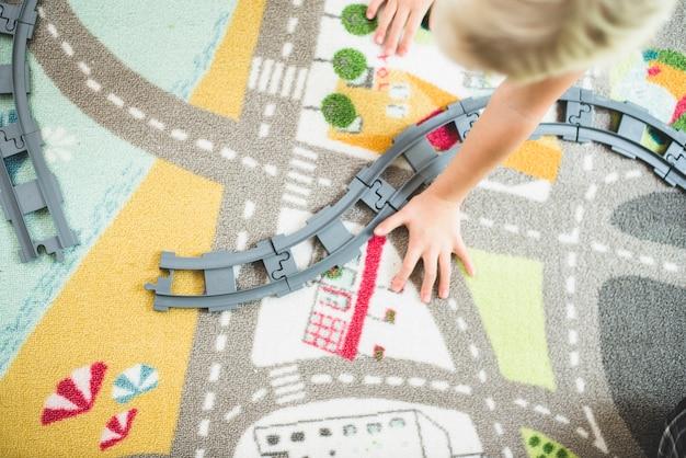 Vue de dessus les enfants qui jouent avec des pistes de train
