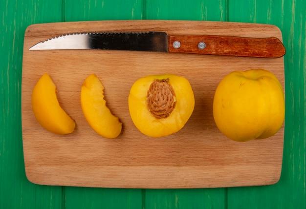 Vue de dessus de l'ensemble des abricots coupés et tranchés avec un couteau sur une planche à découper sur fond vert