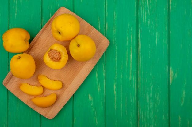 Vue de dessus de l'ensemble des abricots coupés et tranchés sur une planche à découper et sur fond vert avec espace copie