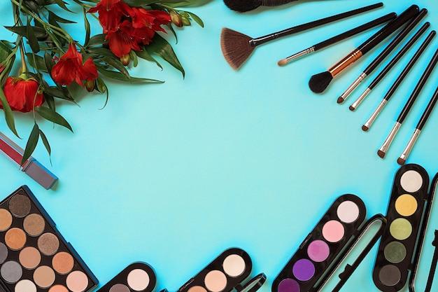Vue de dessus sur l'ensemble de cosmétiques pour maquillage professionnel sur fond bleu. nature morte. espace de copie
