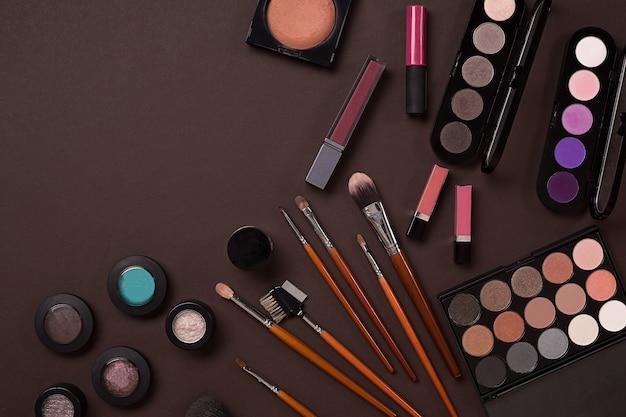 Vue de dessus sur l'ensemble de cosmétiques pour maquillage professionnel sur fond marron. nature morte. espace de copie