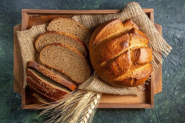 Vue de dessus de l'ensemble et couper du pain noir frais sur une serviette dans un plateau en bois brun sur la surface des couleurs de mélange sombre