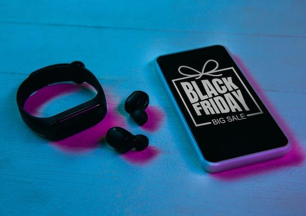 Vue de dessus de l'ensemble de gadgets en néon violet, fond bleu. smartphone, montres connectées, écouteurs. tech, moderne, gadgets, publicité. vendredi noir, cyber lundi, ventes, concept d'achats en ligne de financement