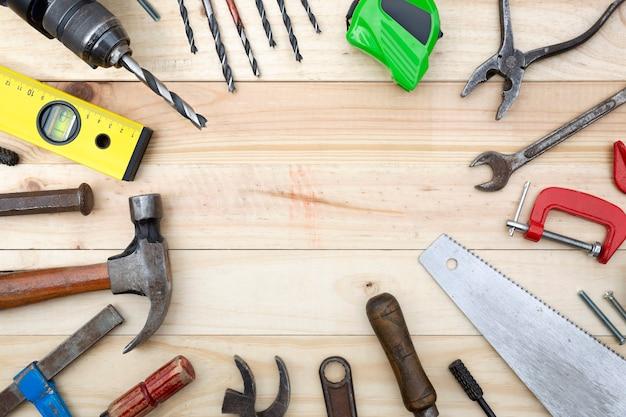 Vue de dessus ensemble d'outils et accessoires d'ébénisterie placés sur une planche de bois de pin naturel avec espace de copie