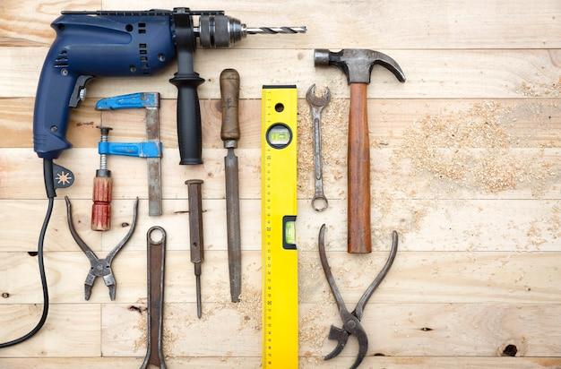 Vue de dessus ensemble d'outils comprenant une perceuse, un marteau et d'autres accessoires de menuiserie placés sur un établi en bois de pin naturel. concept de travail et de bricolage.