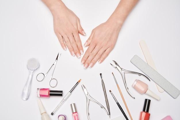 Vue de dessus de l'ensemble d'outils de manucure pour le soin des ongles sur une surface claire - pinceau, ciseaux, vernis à ongles, lime et pincettes