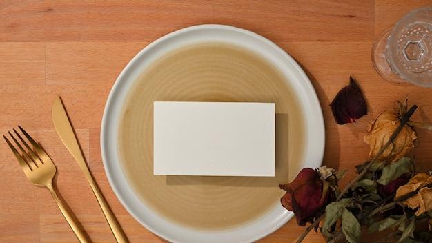 Vue de dessus de l'ensemble de salle à manger avec maquette de carte de visite sur maquette de plaque en céramique et fourchette en laiton et couteau de table