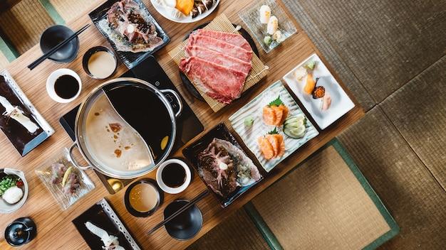 Vue de dessus de l'ensemble shabu comprenant des tranches rares de bœuf wagyu a5, de shabu shoyu et d'une base transparente.