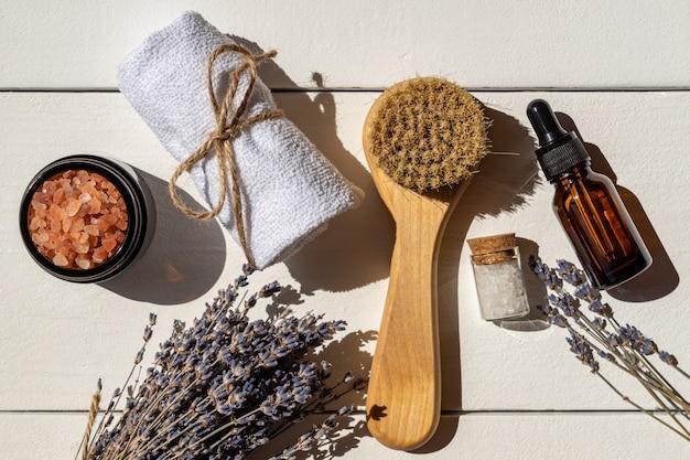 Vue de dessus de l'ensemble de spa visage à la lavande. brosse pour le visage avec poils naturels, serviette en coton, sel rose de l'himalaya et huile essentielle pour le visage ou sérum décoré bouquet sec de fleurs de lavande