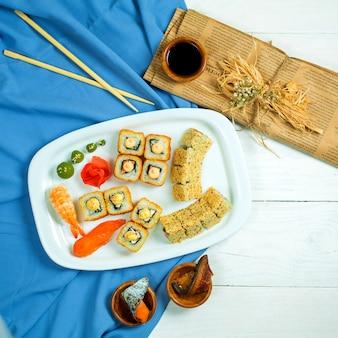 Vue de dessus de l'ensemble de sushi et maki avec sauce soja sur bleu et blanc