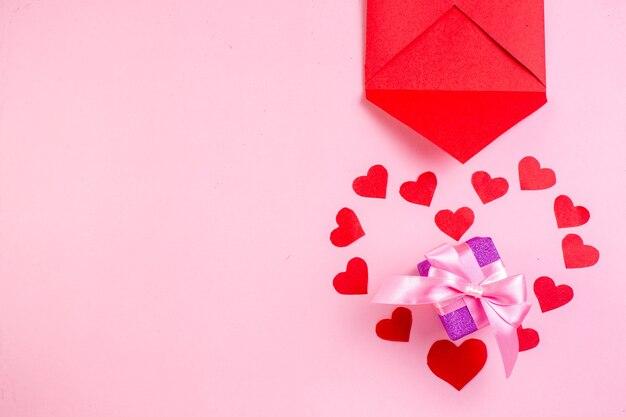 Vue de dessus enveloppe d'autocollants coeur rouge sur fond rose espace libre