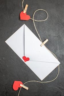 Vue de dessus enveloppe blanche avec note à l'intérieur sur fond sombre amant présent amour couple sentiment mariage couleur coeur