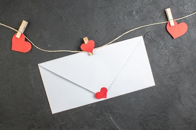 Vue de dessus enveloppe blanche avec note à l'intérieur sur fond sombre amour couple sentiment mariage présent couleur coeur