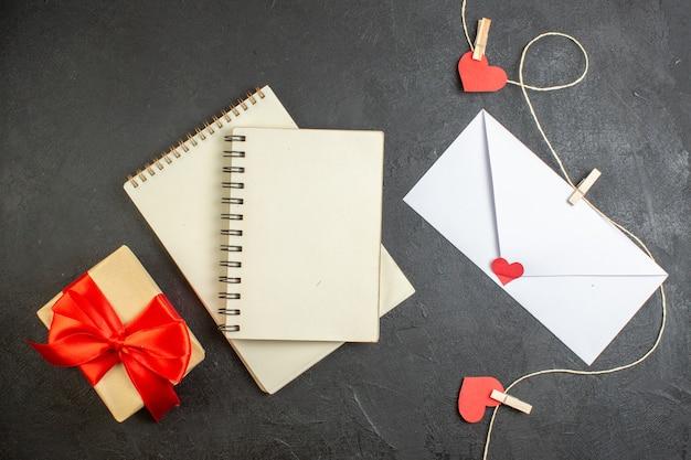 Vue de dessus enveloppe blanche avec note à l'intérieur et présente sur fond sombre amoureux amour couple sentiment mariage couleur coeur