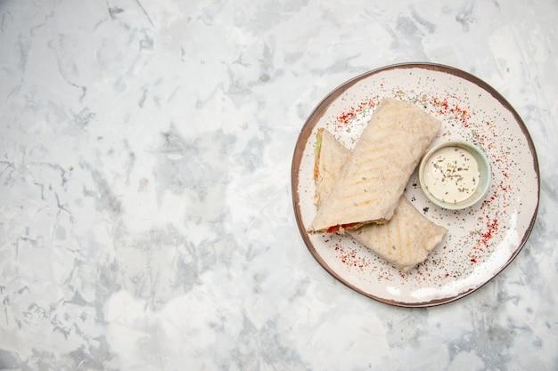 Vue de dessus de l'enveloppe de lavash et du yogourt dans un petit bol sur une assiette sur le côté gauche sur une surface blanche tachée