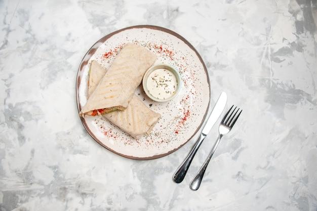 Vue de dessus de l'enveloppe de lavash et du yogourt dans un petit bol sur une assiette et des couverts sur une surface blanche tachée
