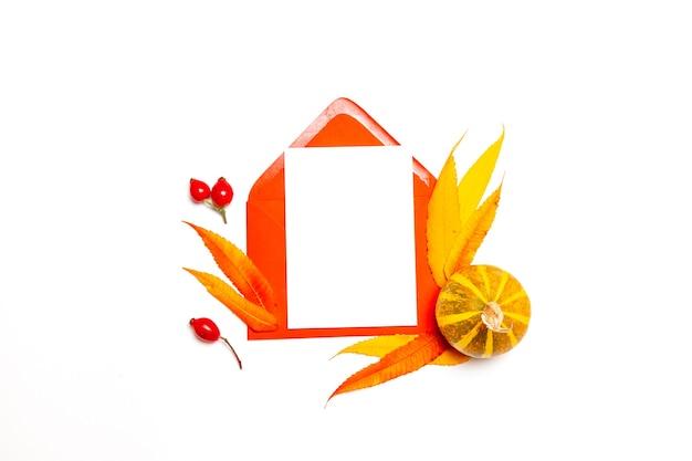 Vue de dessus de l'enveloppe en papier avec maquette vierge et feuilles d'automne, citrouille