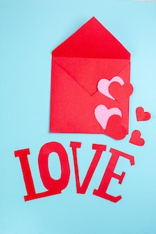 Vue de dessus enveloppe rouge coeurs rouges et roses aiment les majuscules sur table bleue
