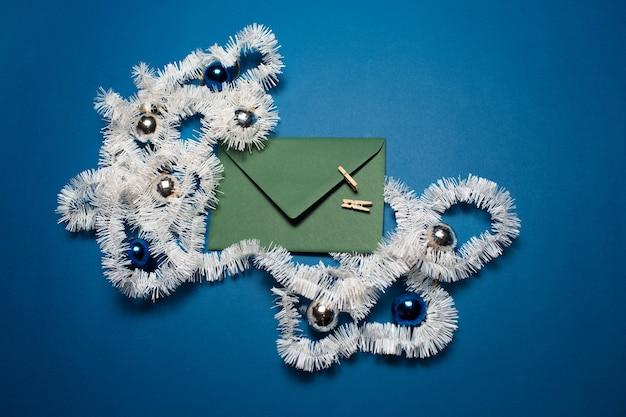 Vue de dessus de l'enveloppe verte décorée d'ornements de noël
