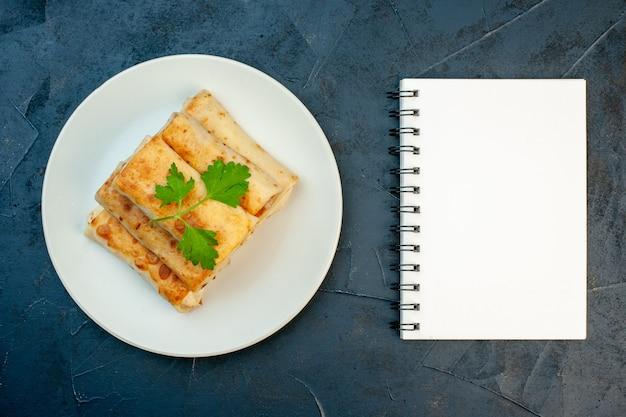 Vue de dessus des enveloppements de lavash frits sur une assiette servie avec un cahier vert et à spirale sur fond sombre