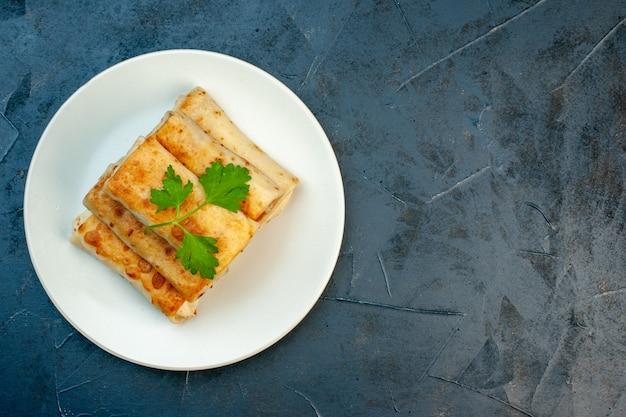 Vue de dessus des enveloppements de lavash frits sur une assiette servie avec du vert sur le côté droit sur fond sombre