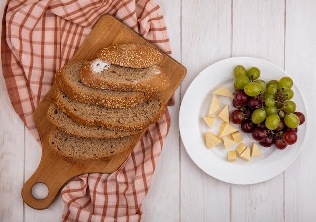 Vue de dessus de l'épi de graines en tranches marron sur une planche à découper sur un tissu à carreaux et une assiette de fromage et de raisin sur fond de bois