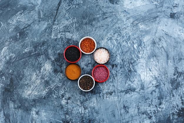 Vue de dessus des épices assorties dans de petits bols sur fond de plâtre gris. horizontal