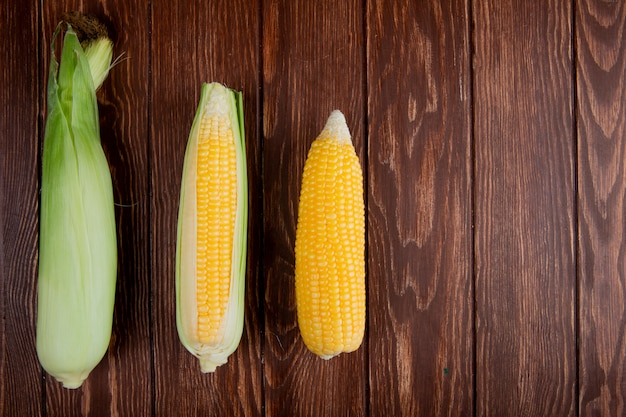Vue de dessus des épis de maïs avec coque sur le côté gauche et surface en bois avec espace copie
