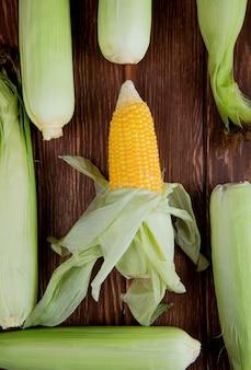 Vue de dessus des épis de maïs avec coque sur une surface en bois