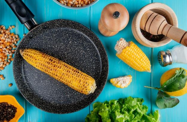 Vue de dessus d'épis de maïs dans une casserole avec des graines de maïs graines de poivre noir couper le sel de maïs citron et laitue autour de la surface bleue