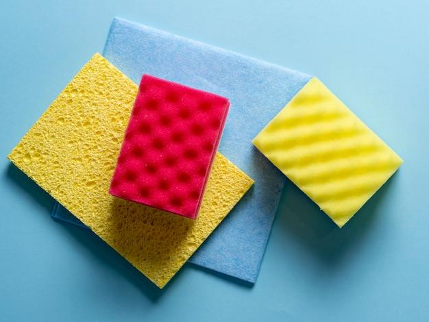 Vue de dessus des éponges de nettoyage de différentes couleurs et tailles