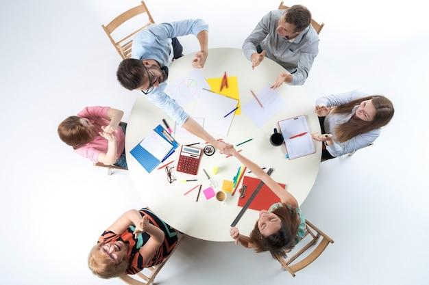 Vue de dessus de l'équipe commerciale de smilimg, assis à une table ronde sur fond blanc. concept de transaction réussie