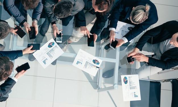 De la vue de dessus. l'équipe commerciale utilise ses smartphones pour travailler avec des données financières.