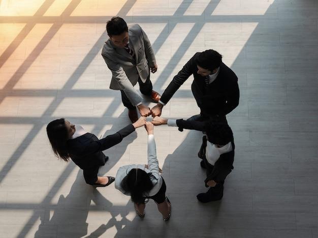 Vue de dessus d'une équipe d'hommes d'affaires divers tenant les poings en cercle, exprimant l'unité et le pouvoir dans le travail d'équipe, des hommes d'affaires multiethniques engagés dans une activité de consolidation d'équipe lors du briefing