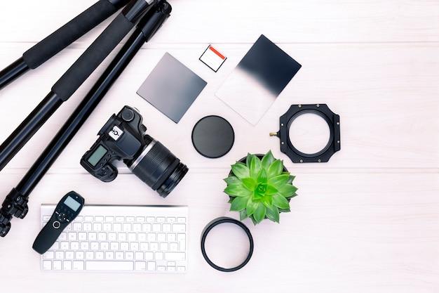 Vue de dessus de l'équipement photographique et accessoires sur une planche de bois blanche