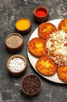 Vue de dessus escalopes frites avec riz cuit et assaisonnements sur la viande de plat de surface sombre