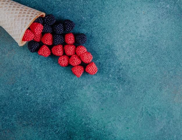 Vue de dessus espace copie marmelade sous forme de framboises et mûres avec un cornet gaufré sur fond vert foncé