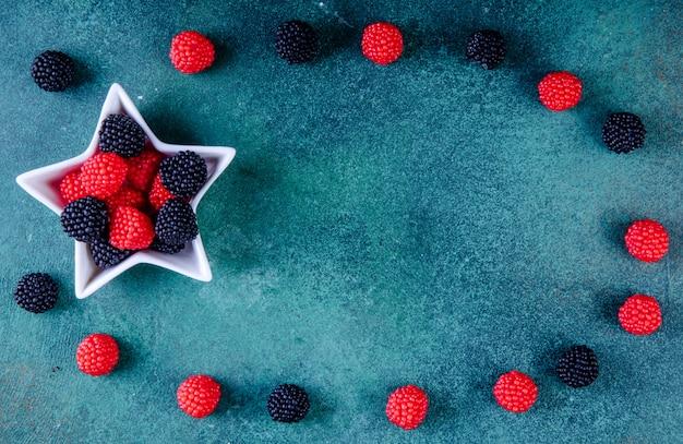 Vue de dessus espace copie marmelade sous forme de mûres et de framboises dans une douille pour confiture en forme d'étoile sur fond vert foncé